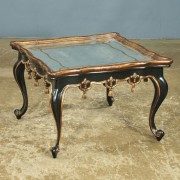 antique glass-topped cocktail table with black lacquer, gold gilding