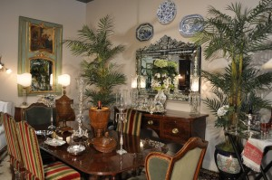 Country French dining room with Sheraton mahogany table and antique sideboard, antique Louis XV walnut bergeres, Venetian mirror, and trumeau mirro